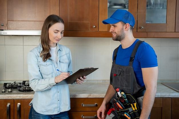 Kundenfrau, die rechnung vom männlichen klempner unterschreibt, der in der küche steht