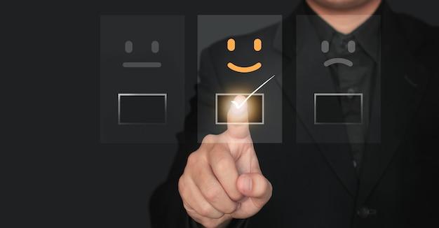 Kundenservice und zufriedenheitskonzept, geschäftsmann berühren den virtuellen bildschirm auf dem glücklichen symbol, das die zufriedenheit des kunden zeigt.