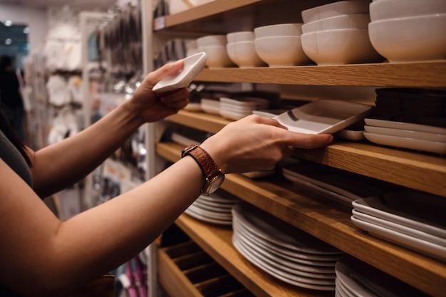 Kundenvergleichsprodukte von rack im shop. junge frau, die dishware wählt