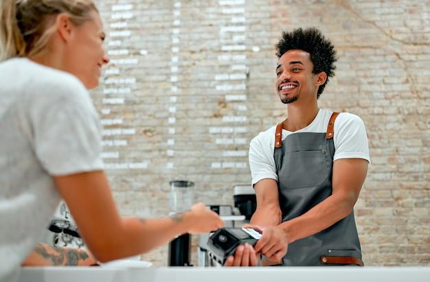 Kundin, die zahlung über handy am schalter im café mit jungem mann leistet. barista hält kreditkartenlesegerät vor weiblichem kunden mit handy.