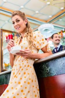 Kundin in kaffeebartrinkbecher cappuccino