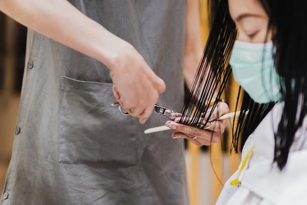 Kundin in medizinischer maske, die sich im friseursalon die haare schneiden lässt