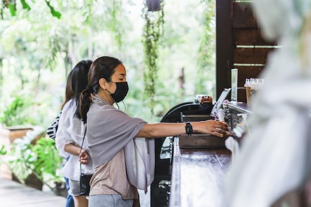 Kundin in schutzmaskenhand greift nach snack im cafe new normal.