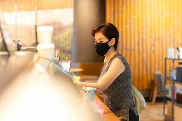 Kundin mit schutzmaske, die rechnung per handy im café bezahlt