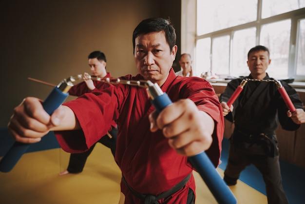 Kung-fu-mann in einem roten kimono, der ein nunchuck in seinen händen hält
