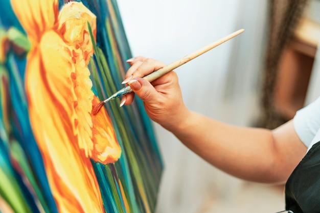 Kunst, das werk des künstlers. junge schöne künstlerin malt ein bild. werkstatt des künstlers. der prozess der kreativität. zeichnen und malen. inventar des künstlers. nahansicht.