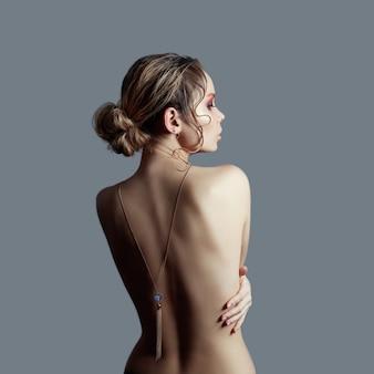 Kunst der nackten mode nackter rücken blond auf grau, anhänger halskette an kette auf dem rücken.