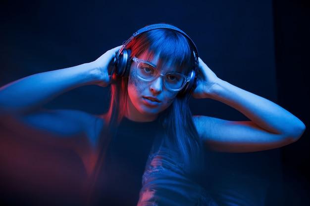 Kunst des cyberpunk. studioaufnahme im dunklen studio mit neonlicht. porträt des jungen mädchens