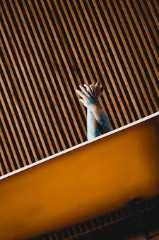 Kunst foto. hände aus dem gelben bad. blaue körperbemalung an den händen. kreativitätskonzept