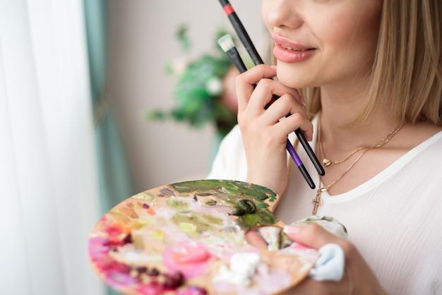 Kunst, kreativität, hobby, beruf und kreatives berufskonzept. künstlerin, die vor fenster aufwirft und mit öl- oder acrylfarbe malt