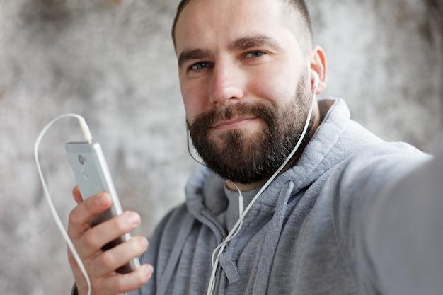 Kunst, menschen, emotionen, musik, 4k und lifestyle-konzept - model released man im studio setzt kopfhörer rockt, elektronisch zur musik. junger gutaussehender bärtiger mann hört musik-smartphone in kopfhörern