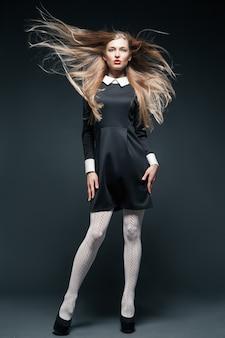 Kunst-modeporträt eines blonden models, das mit im wind flatternden haaren posiert