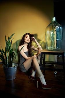 Kunst portrait einer make-up-frau mit reflexion des sonnenlichts auf ihrem gesicht, lichtbrechung durch eine große glasflasche. mädchen sitzt auf dem boden auf gelbem hintergrund