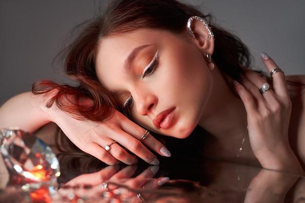Kunst schöne frau mit kreativem make-up liegt auf dem spiegel. schönheitsporträt einer romantischen frau mit schmuck