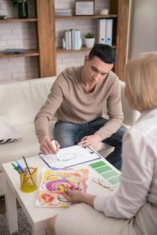 Kunstansatz. nachdenklicher aufmerksamer mann, der psychologen beim zeichnen mit marker besucht