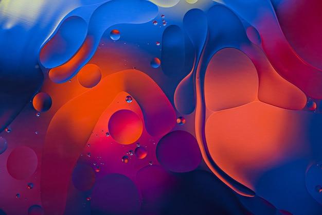 Kunstfarbe neonhintergrund von öltropfen auf wasseroberfläche.