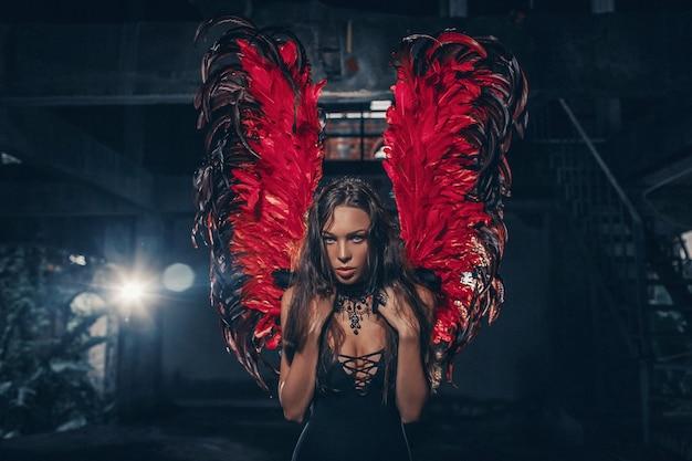 Kunstfoto einer schönen frau des dunklen engels. ein mädchen mit roten teufelsflügeln und einem schwarzen kleid im dunklen raum