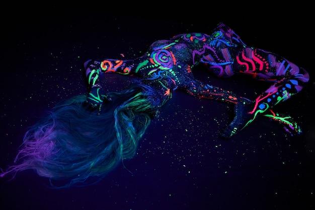 Kunstfrau-körperkunst auf dem körpertanzen im ultravioletten licht. helle abstrakte zeichnungen auf der neonfarbe des mädchenkörpers