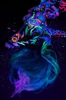Kunstfrau-körperkunst auf dem körpertanzen im ultravioletten licht. helle abstrakte zeichnungen auf neonfarbe des mädchenkörpers