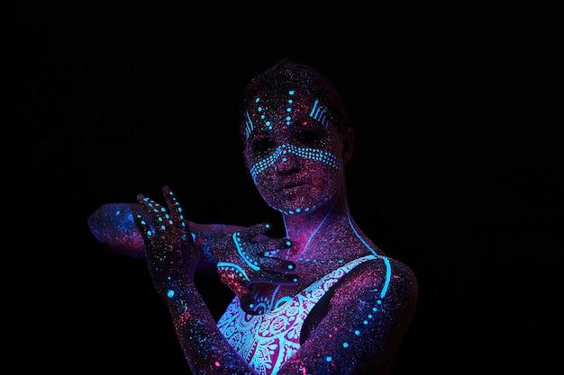Kunstfrauenkosmos im ultravioletten licht. der gesamte körper ist mit farbigen tröpfchen bedeckt. mädchen, das in der dunkelheit aufwirft. lärm, unscharf