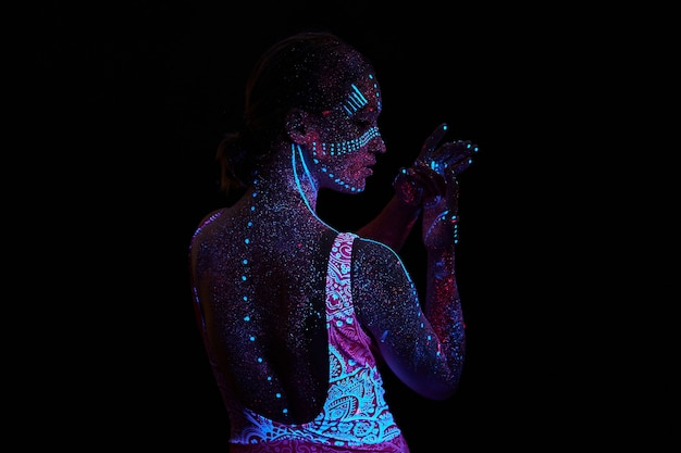 Kunstfrauenkosmos im ultravioletten licht. der gesamte körper ist mit farbigen tröpfchen bedeckt. mädchen, das in der dunkelheit aufwirft