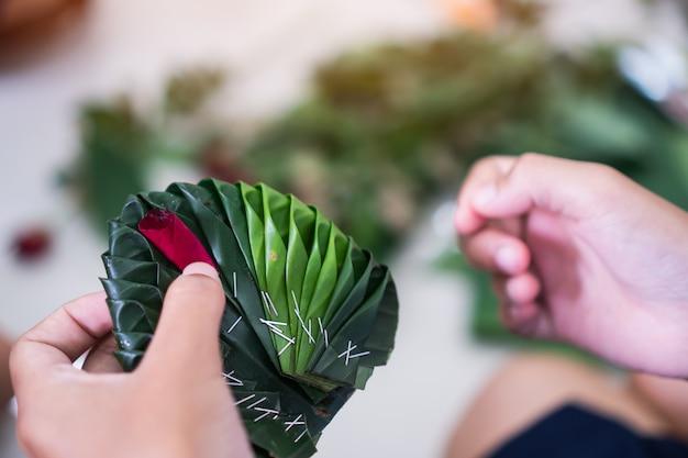 Kunsthandwerk lernen thailändische studenten, grüne bananenblätter zu basteln, die mit blumen geschmückt sind