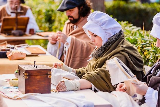 Kunsthandwerker, die im mittelalter verkleidet waren und in einer ausstellung eines festivals altes handwerk zeigten.