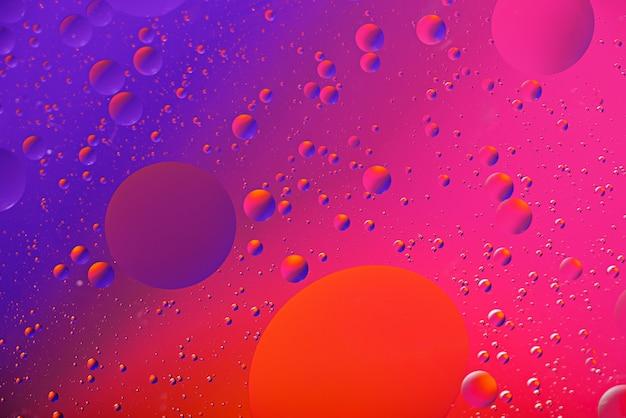 Kunsthintergrund von öltropfen auf der wasseroberfläche auf buntem gradientenhintergrund für tapete, fahne