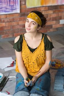 Kunsthobby. porträt der jungen dame, die auf boden im studio sitzt, hände schmutzig mit farbe, pinsel haltend.