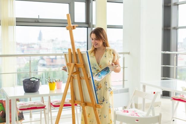 Kunsthochschule, kunsthochschule, ausbildung für eine gruppe junger studenten. glückliche junge frau lächelnd, mädchen lernen zu malen.