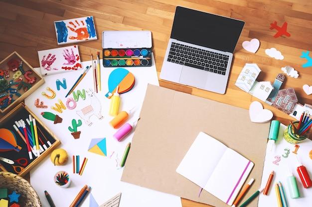 Kunstkinderrahmen mit leerem papier des laptops und zubehör für kreatives gestalten