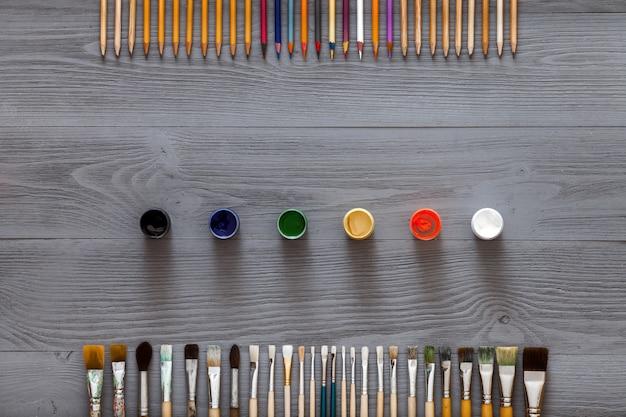 Kunstkreativer tischhintergrund mit versorgungswerkzeugen auf grauem hölzernem schreibtisch