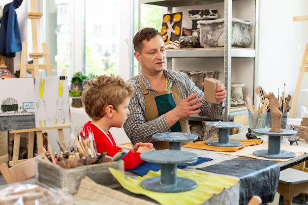 Kunstlehrer, der kleinen jungen über das formen von tonfiguren erzählt