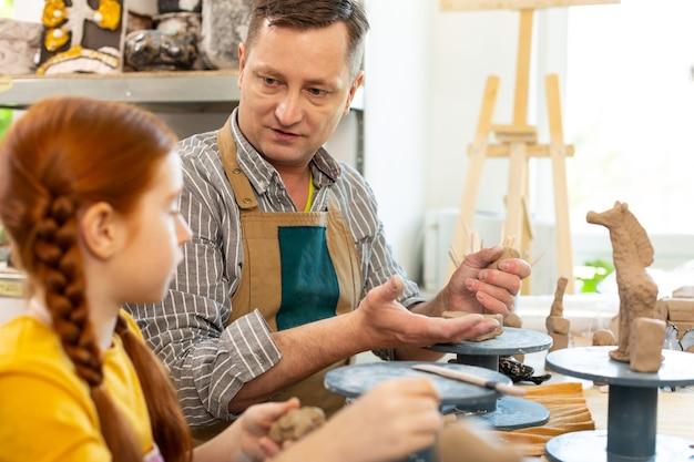 Kunstlehrer mit schürze im gespräch mit seinem kleinen schüler