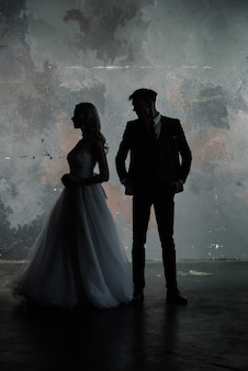 Kunstmode-studiofoto des brautpaarschattenbild-bräutigams und der braut auf farbhintergrund. kunsthochzeitsstil.