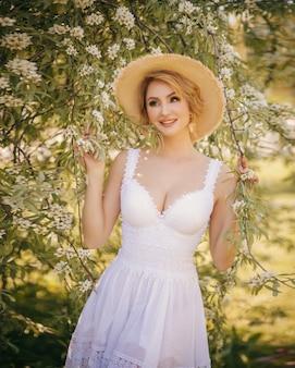 Kunstmodeporträt schönen jungen blondine in einem blühenden garten des sommergrüns in einem kleid des weißen lichtes, in einem strohhut. mädchen im landhausstil