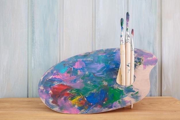 Kunstpalette aus holz mit farben und pinseln