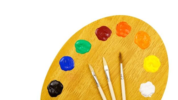 Kunstpalette mit farben und pinseln lokalisiert auf weißer wand.