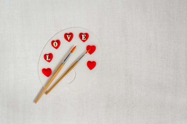 Kunstpalette mit roten herzen, buchstaben liebe und bürsten auf weißem hölzernem hintergrund.