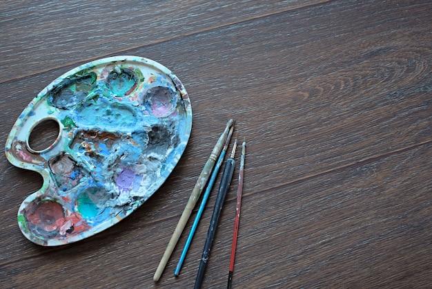 Kunstpalette und pinsel für das malen auf hölzernem hintergrund. die aussicht von oben.
