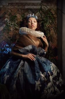 Kunstporträt einer mädchen prinzessin queen im laub und im grün, fabelhaftes romantisches bild einer asiatin in einem magischen kleid. sinnlicher sanfter blick. das mädchen im palast wartet auf den prinzen