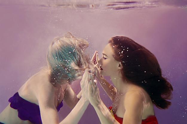 Kunstporträt von zwei schönen hübschen frauen, die sich die hände unter wasser auf rosafarbenem hintergrund halten
