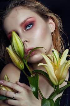 Kunstschönheitsmädchen-gesichtsnahaufnahme mit lilien in den händen
