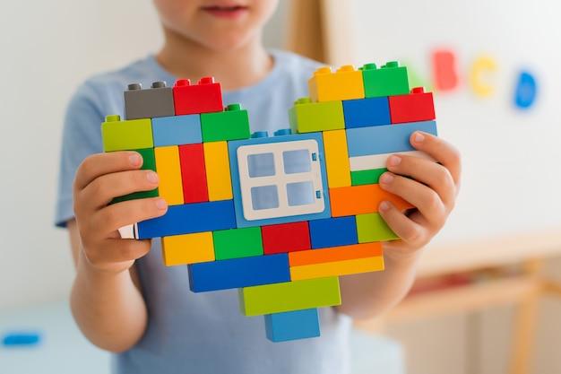 Kunststoff-bauklötze, designer-kinderspielzeug. helle bausteine formen die hände der herzkinder.
