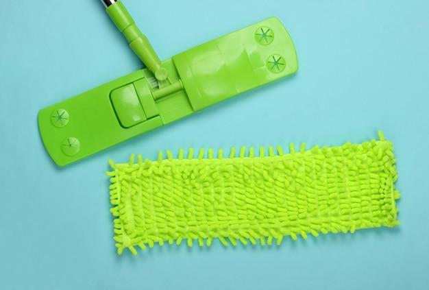 Kunststoff grüner mopp auf blauer oberfläche. desinfektion und reinigung im haus. draufsicht