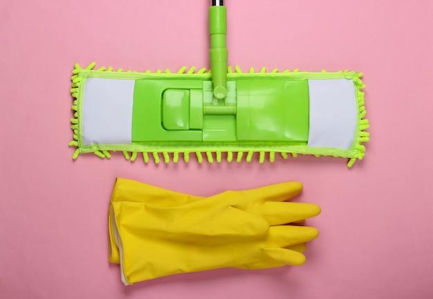 Kunststoff grüner mopp, handschuhe auf rosa oberfläche. desinfektion und reinigung im haus. draufsicht