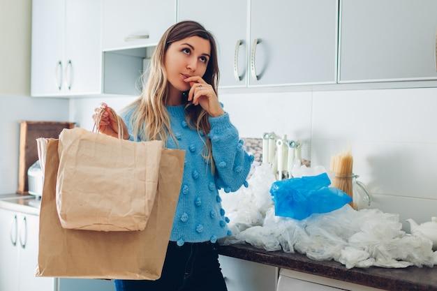Kunststoff- oder papiertütenauswahl. hausfrau frau, die öko oder polyethylenpaket zu hause wählt