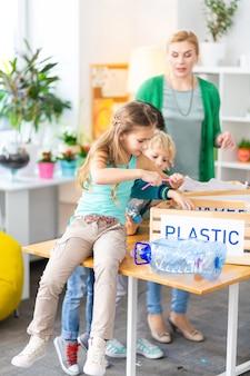Kunststoff sortieren. schönes mädchen, das in der schule auf dem tisch sitzt und plastik mit klassenkamerad und lehrer sortiert
