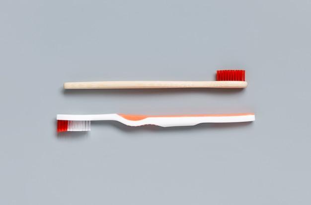 Kunststoff- und bambuszahnbürsten auf grauer hintergrundoberansicht