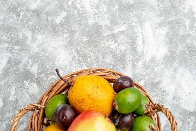 Kunststoff-weidenkorb in der oberen hälfte mit apfelbirnen, feykhoas-pflaumen und kaki auf dem grauen tisch mit freiem platz